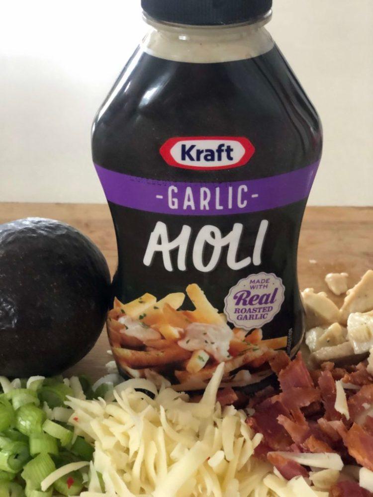 bottle of Kraft brand Garlic aioli with cheese, bacon, green onions, chicken and am avocado near it