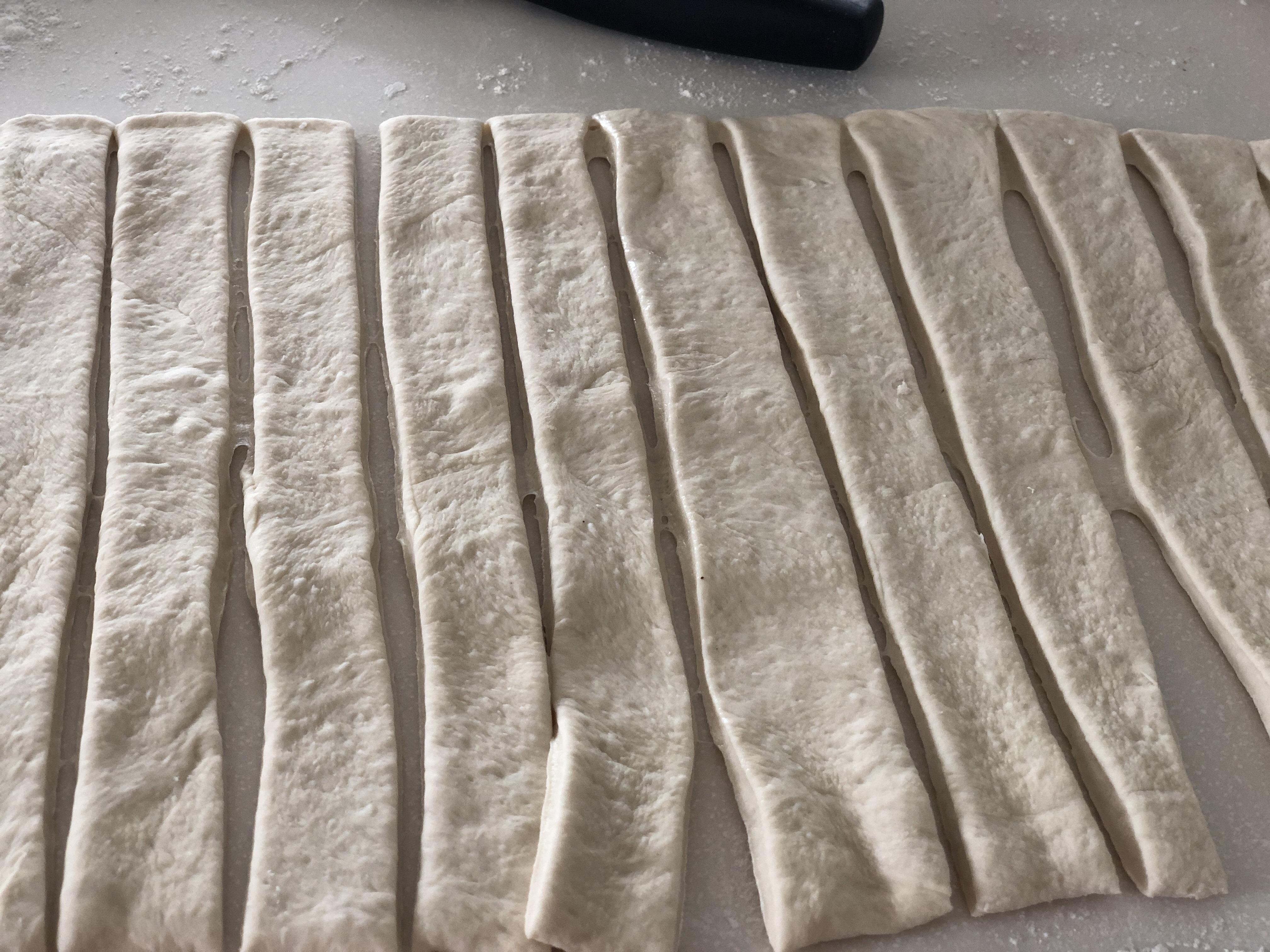 Breadstick dough cut into strips to make breadsticks
