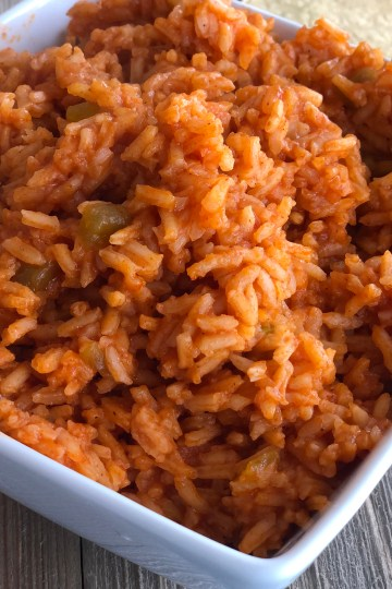 Mexican Rice in a white dish with a serving spoon