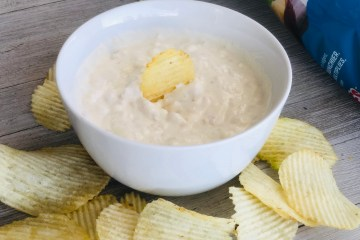 Clam Dip in a bowl with potato chips surrounding it
