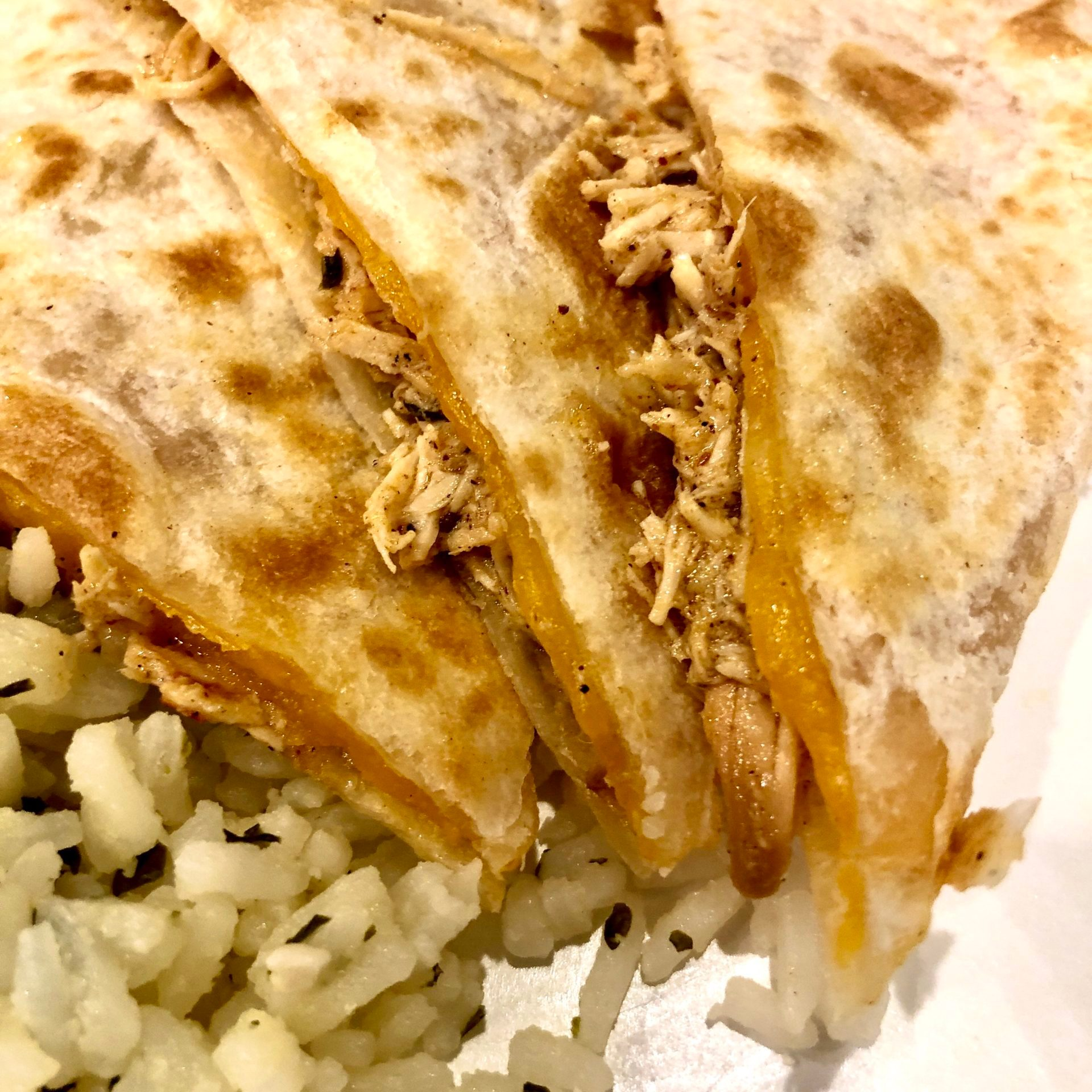 Copycat Cafe Rio Slow Cooker Chicken in a cheesy quesadilla served with cilantro lime rice