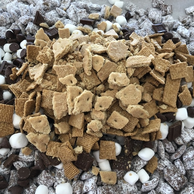 Graham Cracker pieces are added to the S'mores Muddy Buddies snack mix