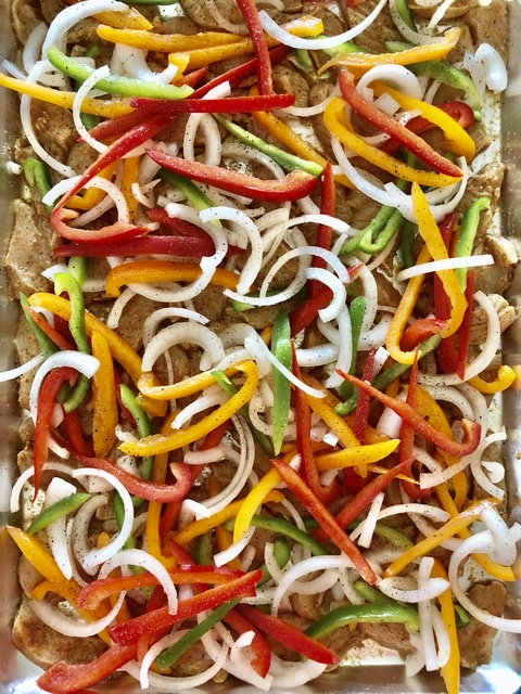 sliced onion and bell peppers on top of the marinaded chicken for sheet pan chicken fajitas