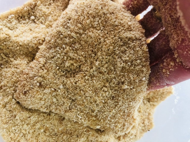 coating chicken breast pieces in breadcrumbs