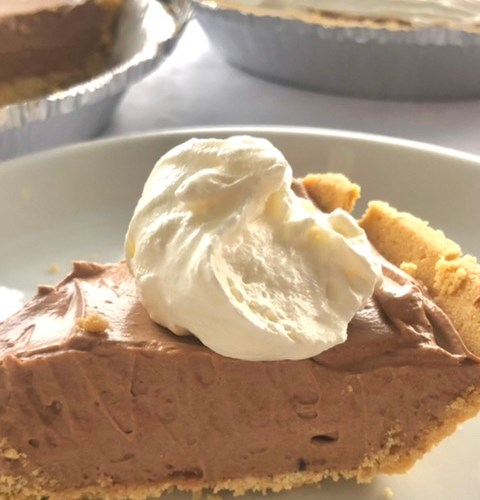 A slice of easy chocolate cream pie with homemade whipped cream on top in a graham cracker crust