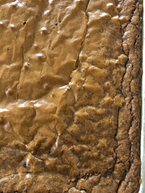 up close shot of baked brownies with shiny top and crinckly edges