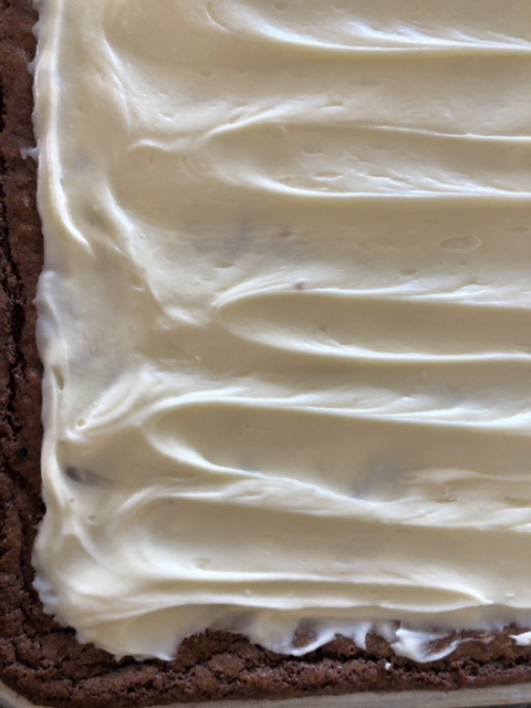 up close shot of cream cheese frosted brownies