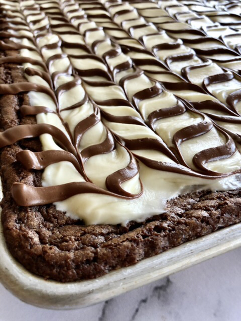 up close shot of the corner of the sheet pan brownies frosted with cream cheese frosting and a chocolate drizzle