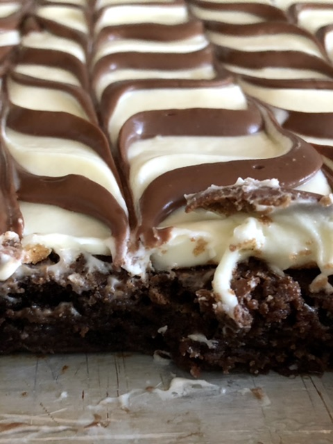 close up of sheet pan of brownies showing with peices of being cut from the pan showing a fudgy brownie under the cream cheese frosting
