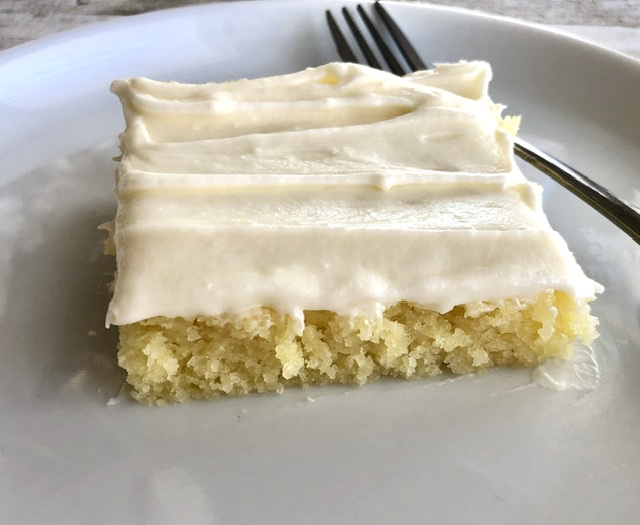 a closeup shot of the yellow lemon sheet cake with lemon cream cheese frosting and a fork laying next to the piece of cake