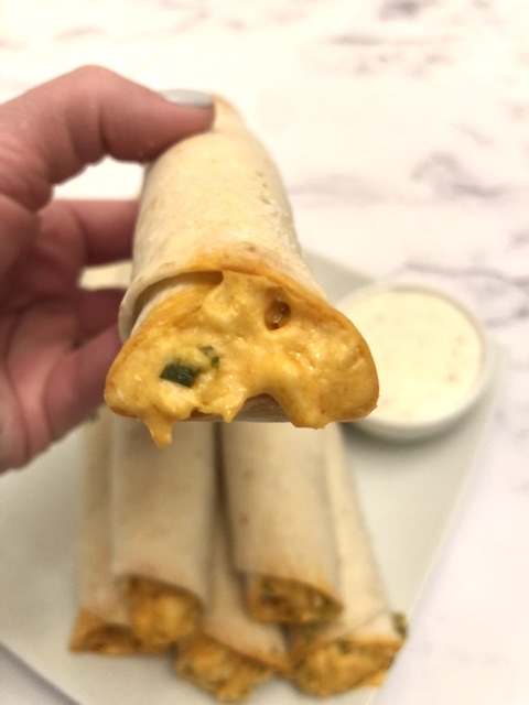 buffalo chicken ranch wrap held in a hand showing the filling with a side of ranch in the background for dipping