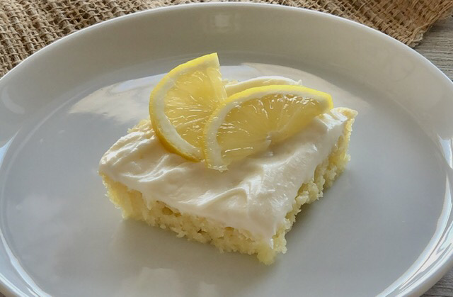 a piece of lemon sheet made with fresh swueezed lemons frosted with cream cheese frosting that is also made with fresh lemons and a lemon slice on top of the cake for garnish