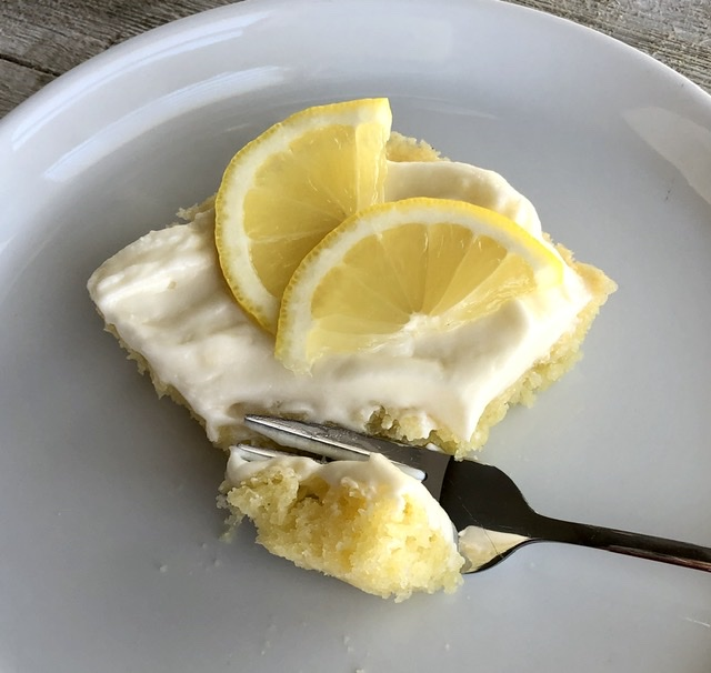 a fork cutting into the lemon sheet cake for a bite