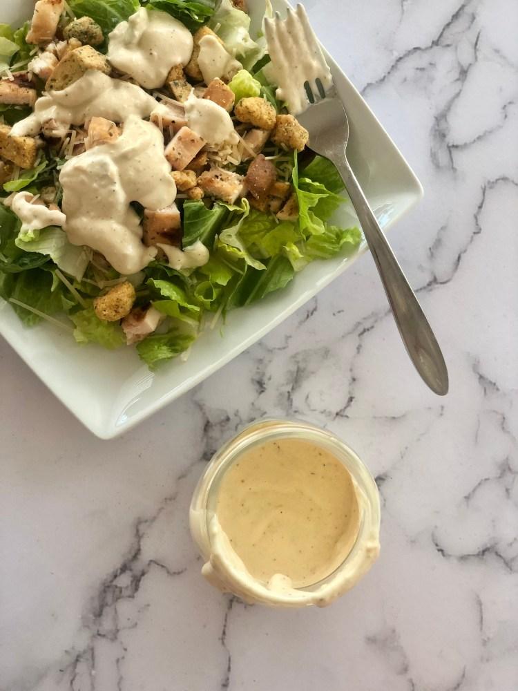 Homemade Caesar Salad Dressing in a jar next to salad
