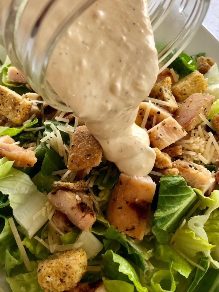 Homemade Caesar Salad Dressing poured on a salad