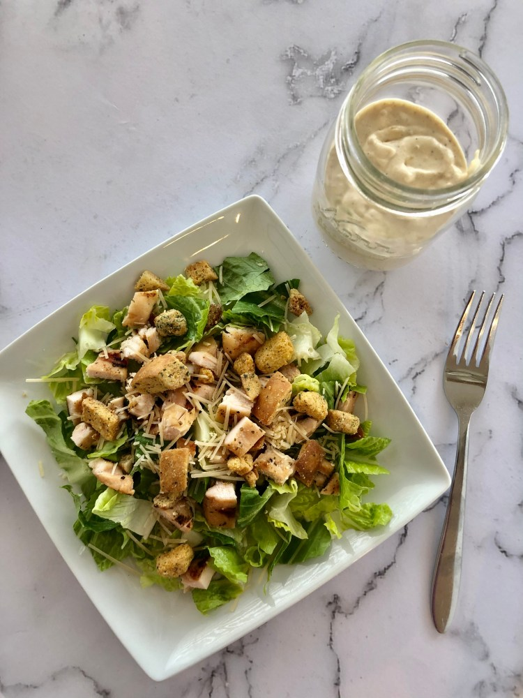 Chicken salad in a dish and a jar of Homemade Caesar Salad Dressing next to it