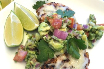 Grilled Chicken with avocado salsa on a white plate for serving with cilantro and limes for garnish