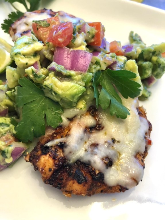 Grilled chicken topped with melted cheese and avocado salsa on a white plate ready to eat
