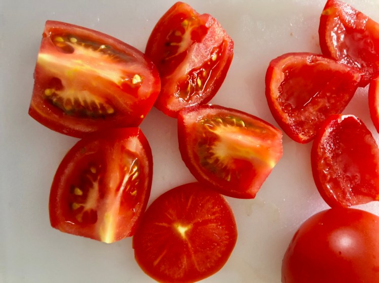 tomatoes quartered and some tomatoes with the seeds removed ready to chop
