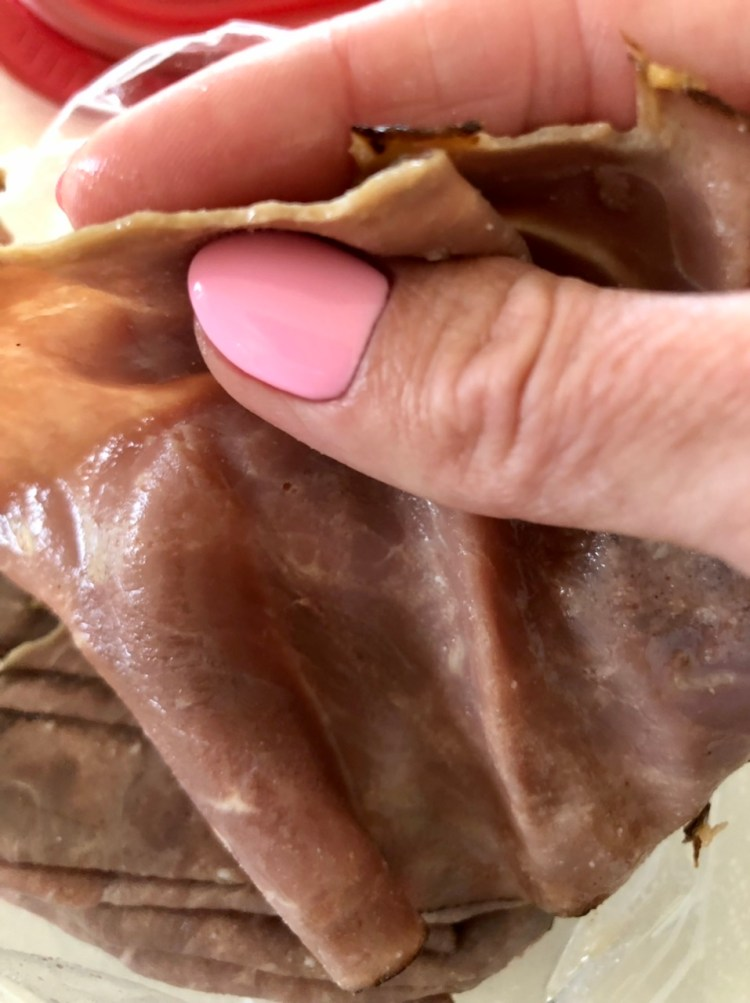 think sliced raost beef, a hand showing the thin cut of the roast beef