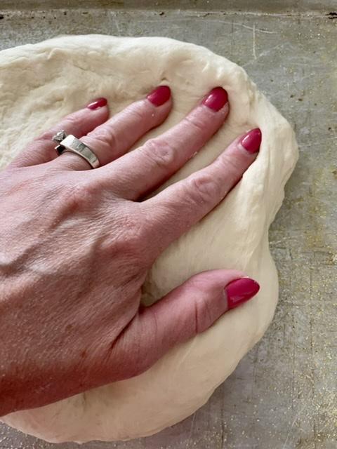 hand pressing pizza dough into a half sheet pan for sheet pan pizza