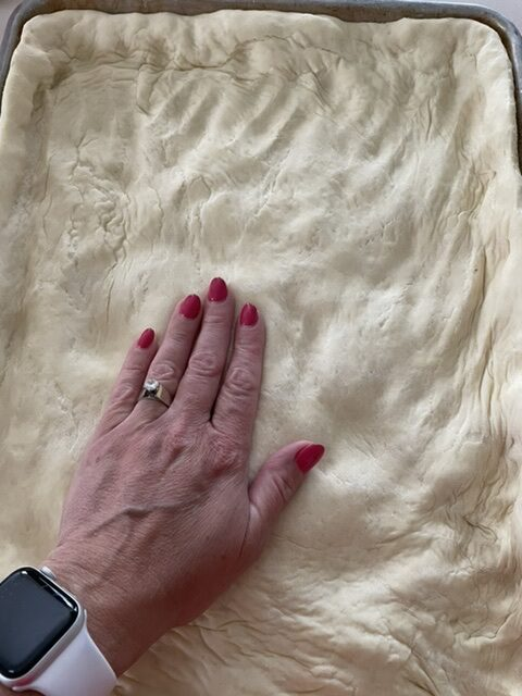 a hand pressing down the puffy raised pizza dough