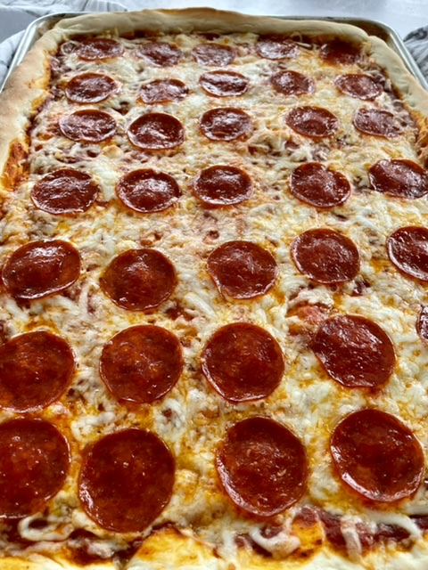 Sheet pan pizza with pepperoni on it