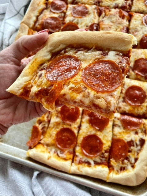 hand holding a slice of sheet pan pizza