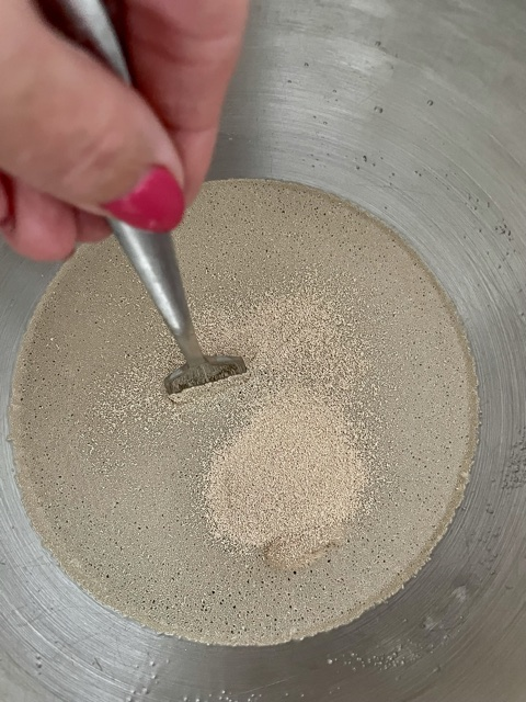 stirring the yeast into the warm water and sugar to make pizza dough