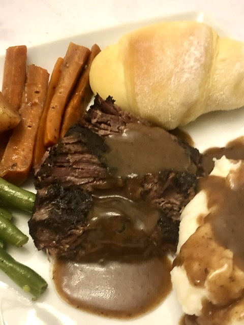 plate of beef roast with gravy, carrots, potatoes, green beans and a roll