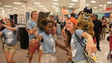 Laila Grayson (left) and Lindsey Gemmill (right) dance along with Hink and other student orientation guides. Photo by Amy Street