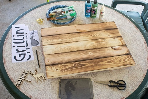 outdoor table with board and paint ready for crafting