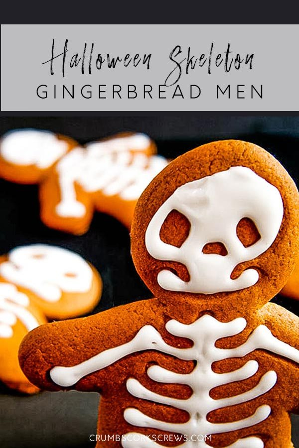 gingerbread man style cookie with his skeleton in icing - standing in front focus.  A couple of other cookies laying in the background.