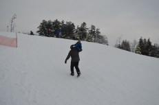 Dad carrying Aiden up the Hill to sled down