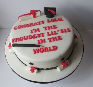 Graduation cake with scrolls and cap toppers