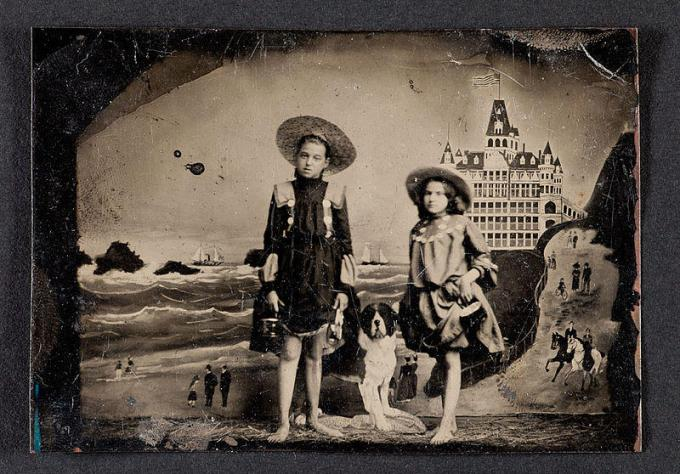 Tintype of two girls in front of a painted background of the Cliff House and Seal Rocks in San Francisco, ca. 1900
