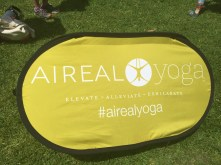 Excellent branding and portable sign staked into the grass #airealyoga