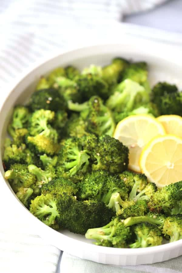 roasted broccoli recipe in a white baking dish with garlic and lemon