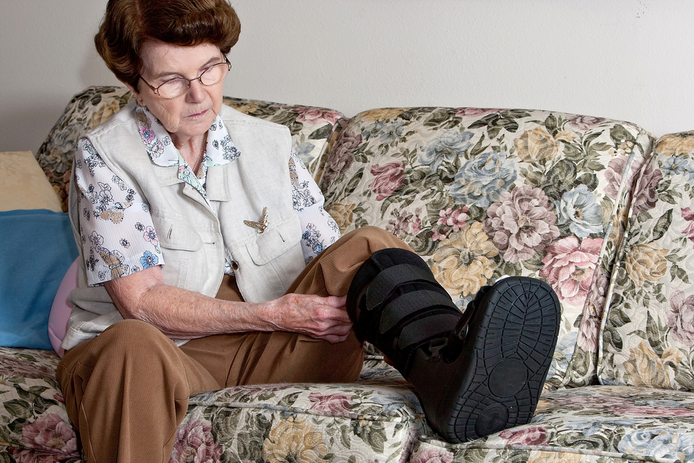 a woman sitting on a couch putting on a medical boot to protect her fractured foot