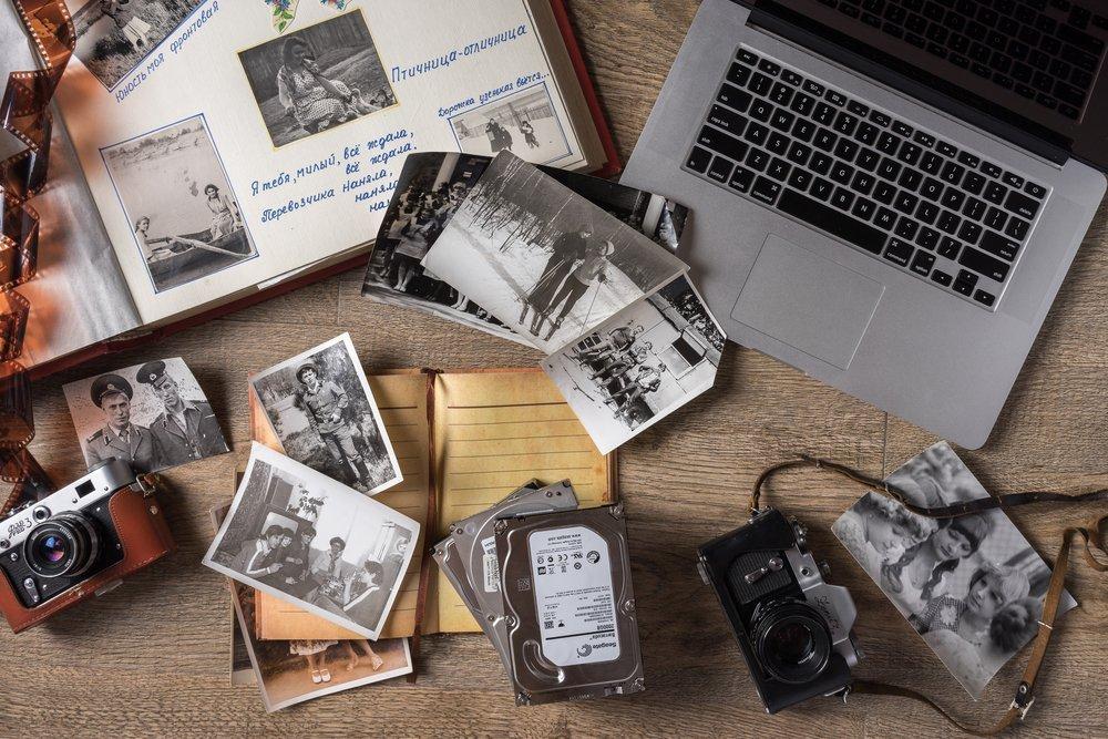 Vintage family photos in an album next to a laptop