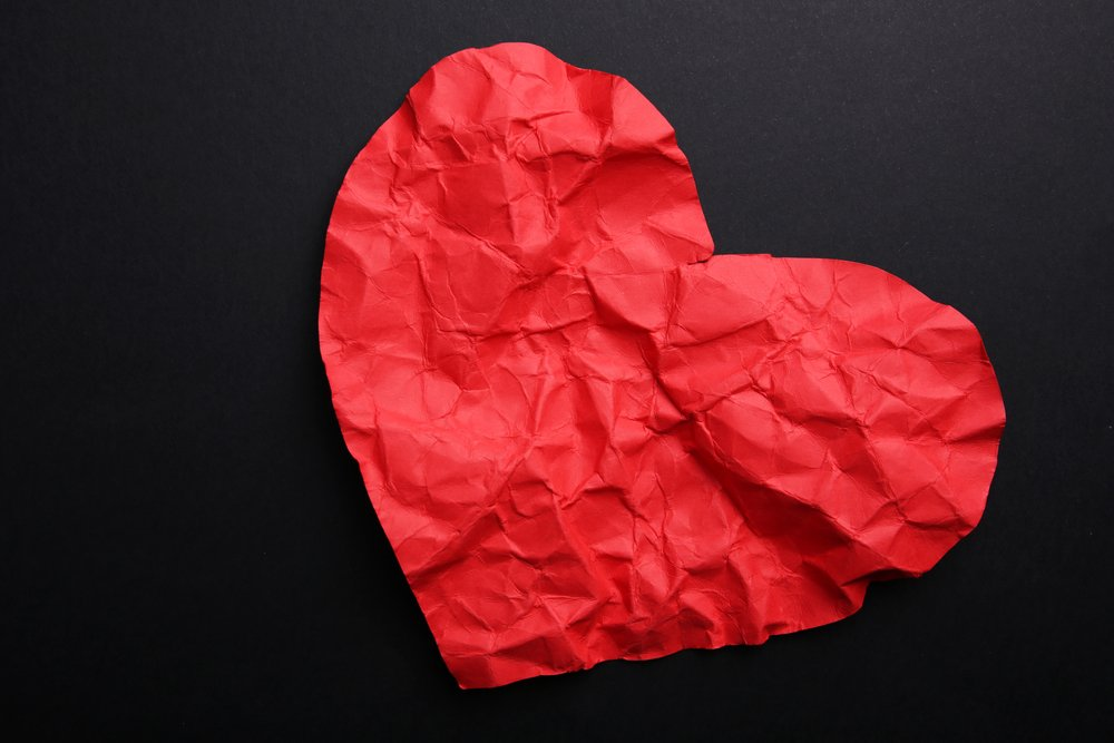 Crumpled paper heart on black background