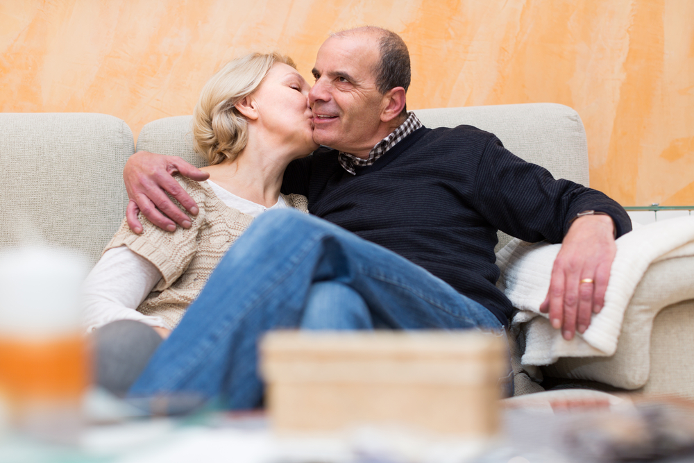 Happy smiling mature husband and wife cuddling on couch at home. Focus on woman