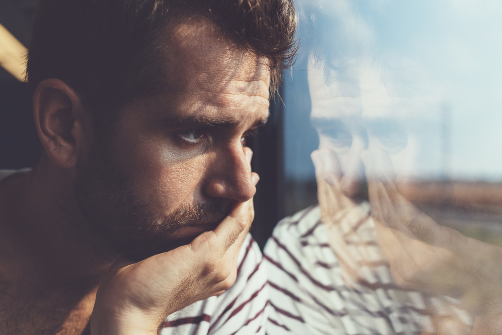 young male caregiver overwhelmed by negative thoughts and in need of coping mechanisms