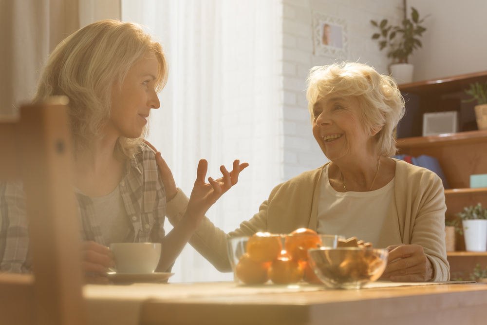 Woman sitting beside table while talking with her old mother