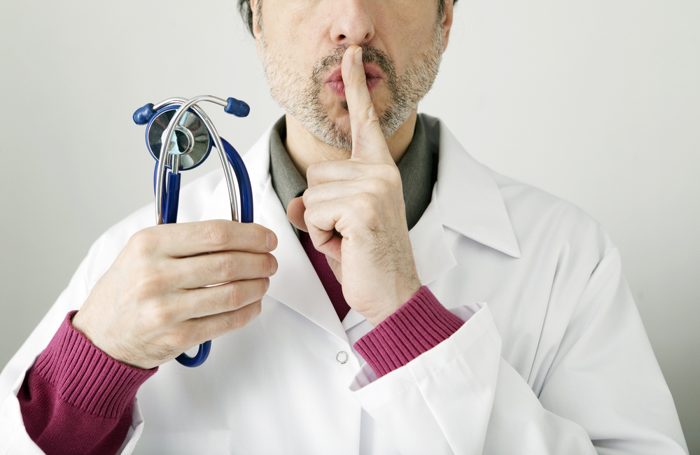 white male doctor holding stethoscope in one hand and gestures for silence with the other hand
