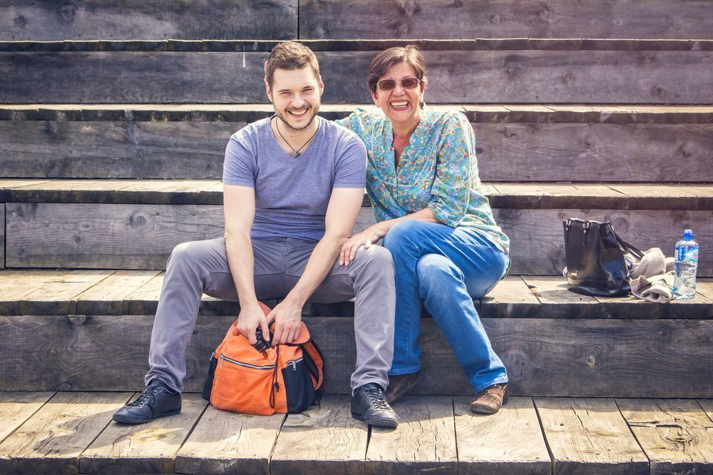 mother and son posting for a snapshot outside on wooden bleachers, demonstrating the ways family members care for one another outside of the formal healthcare setting
