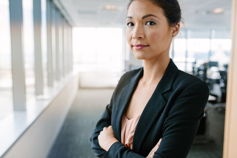 Portrait of mature businesswoman standing in office with her arms crossed. Asian female entrepreneur in suit looking at camera confidently.