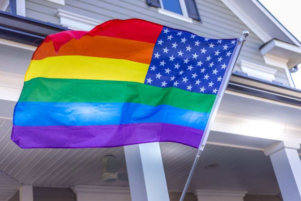 Pride rainbow American flag swaying in the wind on a vinyl siding upper middle class luxury single family home building in the background