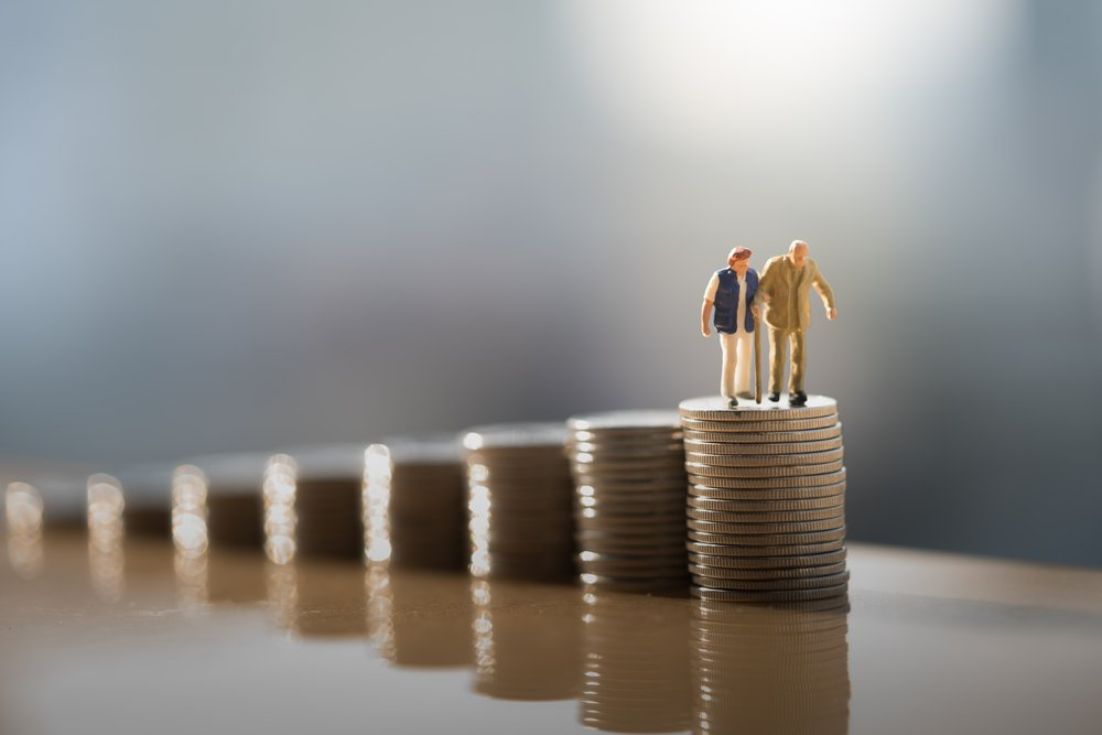 figurines of an elderly couple on a stack of coins, facing a cliff with nowhere to go