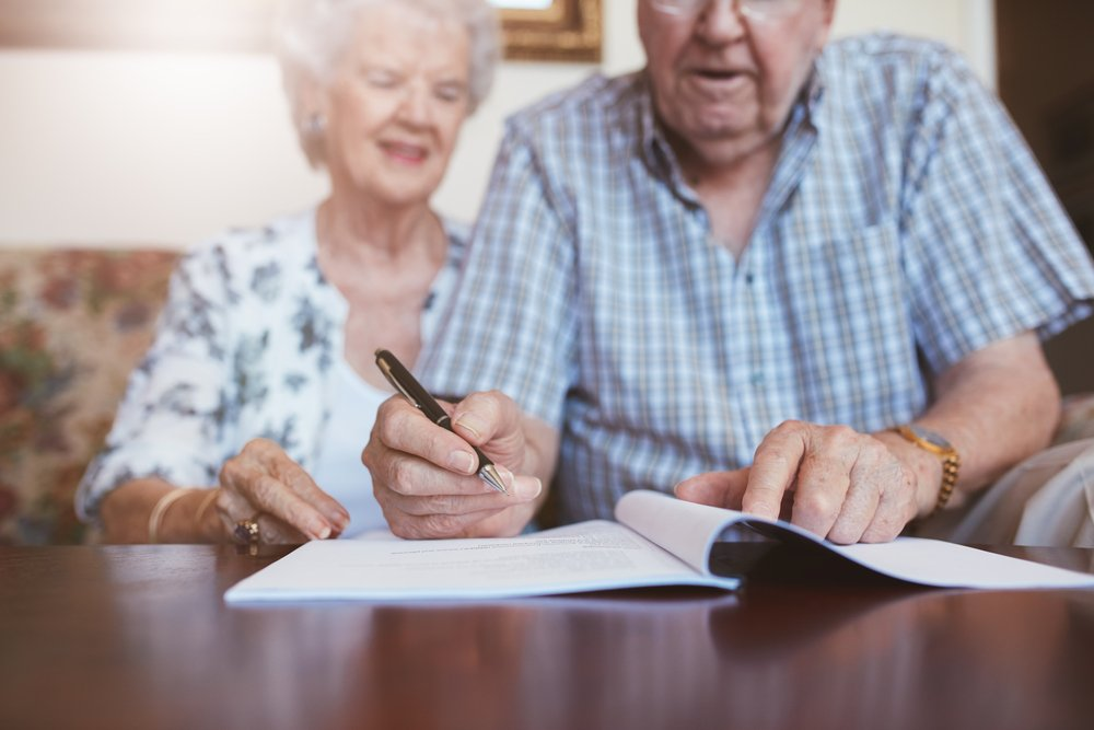Senior couple signing will documents. Elderly caucasian man and woman sitting at home and signing some paperwork, focus on hands